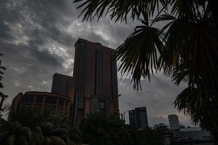 Bottom view of modern skyscrapers over cloudy sky in Kuala Lumpur, Malaysia Редакционное