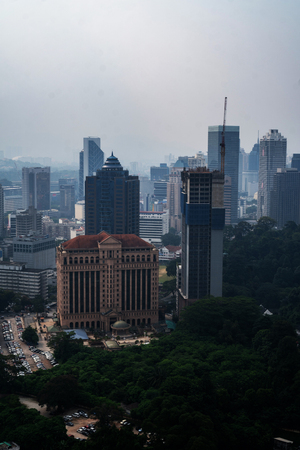 Aerial drone view of Kuala Lumpur city skyline during cloudy day, Malaysia