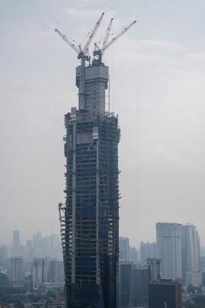 Aerial drone view of unfinished skyscraper over cloudy sky in Kuala Lumpur, Malaysia