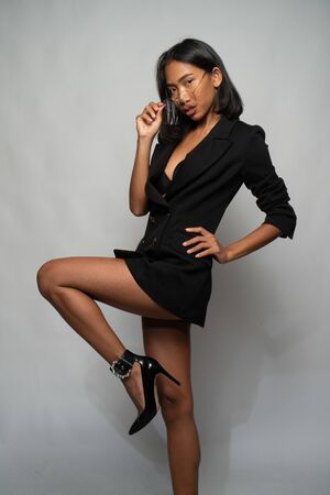 Portrait of attractive young Asian woman in elegant black blazer, high heels and glasses posing over light gray wall background