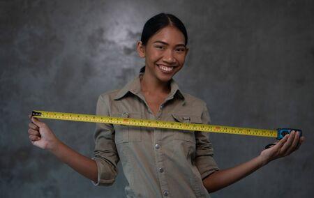 Ritratto dell'architetto asiatico sorridente della donna in nastro di misurazione della tenuta dell'uniforme sopra il muro di cemento. Concetto di lavoro