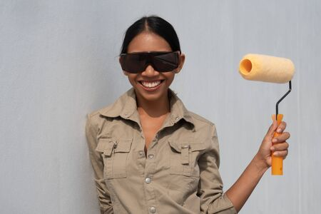 Portrait of attractive young girl builder with paint roller in overall and protective glasses smiling isolated over white wall background Banco de Imagens