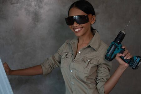 Portrait of attractive young girl builder with drill in overall and protective glasses standing on the ladder  over concrete wall background