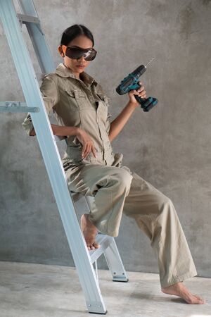 Attractive young girl builder with drill in overall and protective glasses sitting on the ladder  over concrete wall background