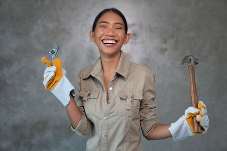 Portrait of attractive young girl builder with wrench and hammer in overall and gloves smiling over concrete wall background