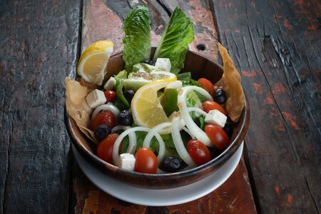Greek salad with fresh vegetables, feta cheese and black olives isolated on rustic wooden kitchen table