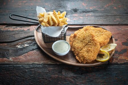 Fish and chips isolated on rustic wooden table