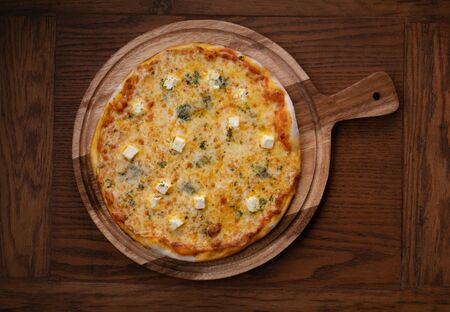 Top view of fresh tasty Four cheeses pizza on wooden background