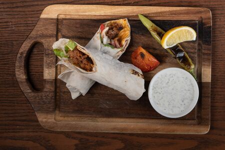 Turkish and Arabic traditional Ramadan Adana kebab roll wrap serving with yogurt and hot pepper isolated on wooden background Stock Photo