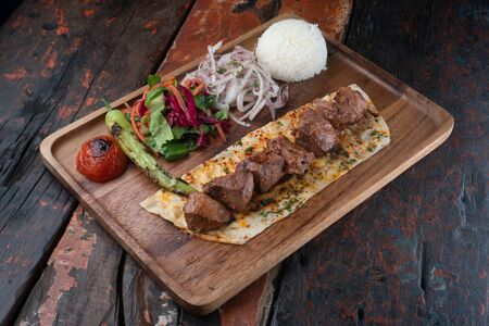 Turkish lamb sis kebab with rice and vegetables isolated on rustic wooden table