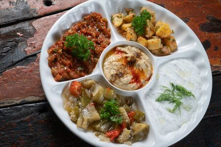 Mix plate Arabic food with vegetarian spread starters isolated on rustic wooden background Zdjęcie Seryjne