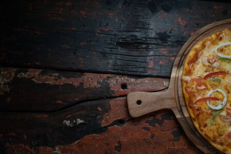 Top view of fresh tasty pizza with seafood, tomato, paprika and mozzarella cheese isolated on rustic wooden background. Copy space