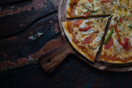 Closeup top view of fresh tasty pizza with chicken, tomato, paprika and mozzarella cheese isolated on wooden background