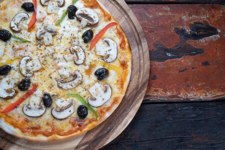 Top view of fresh tasty pizza with mushrooms, olives, paprika and mozzarella cheese isolated on rustic wooden table