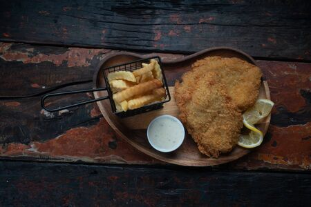 Top view of fish and chips isolated on rustic wooden table Фото со стока