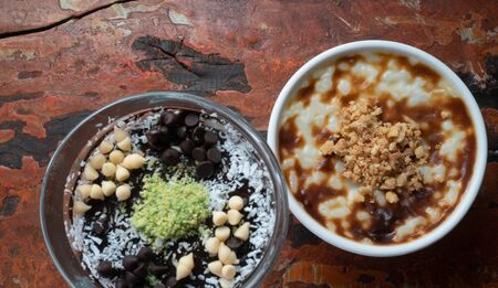 Closeup top view of Turkish chocolate mousse pudding and rice pudding with walnut isolated on rustic wooden table