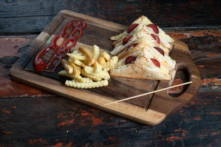Sandwiches with Turkish sausage (sucuk) and cheese served aise with french fries isolated on rustic wooden table