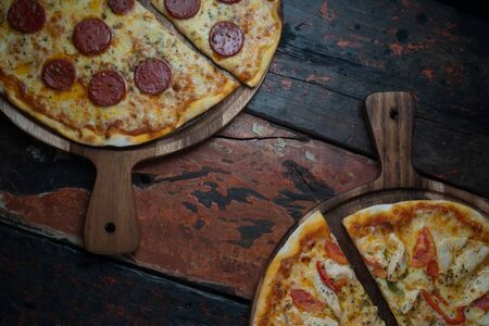 Top view of fresh tasty pizzas on wooden background. One pizza with Turkish sausage and mozzarella cheese, other with chicken, paprika and tomato isolated on wooden rustic table