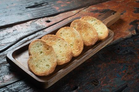 Toasted baguette slices isolated on rustic wooden kitchen table 免版税图像