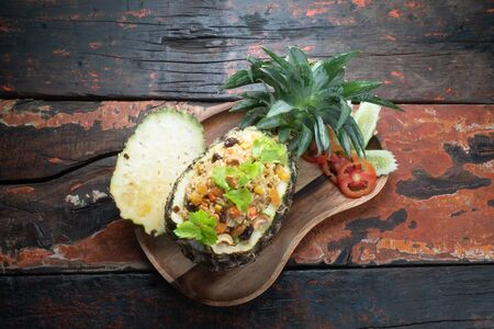 Top view Thai food pineapple chicken fried rice isolated on rustic wooden table Stockfoto