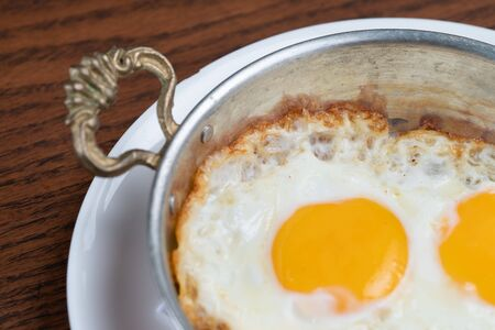 Closeup of fried egg in copper pan isolated on wooden table