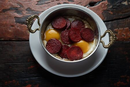 Turkish Sausage (sucuk) and egg isolated on rustic wooden table Stockfoto