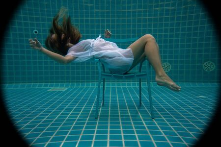 Beautiful woman with long red hair posing underwater on the chair Imagens