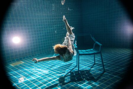 Beautiful woman with long red hair posing underwater next to the chair in white dress