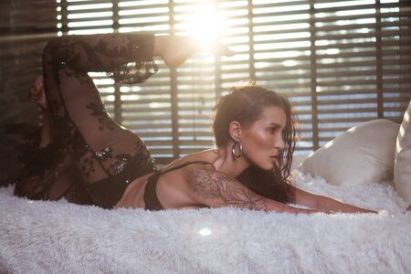 Sensual woman wearing black bra and trousers posing on the bed over window with blinds background