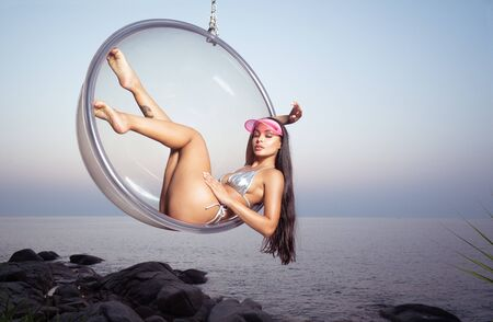 Fashion girl in silver bikini and pink visor posing outdoors on glass chair over sky and sea background during sunset