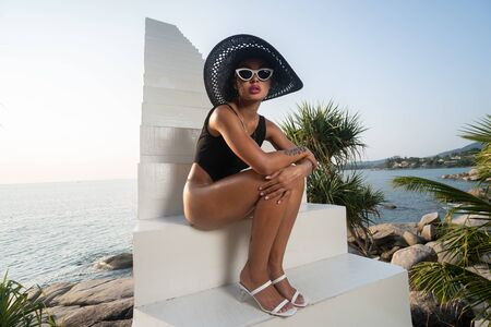Fashion girl in black swimsuit, hat and sunglasses posing outdoors on the stairs over sky and sea background Stockfoto