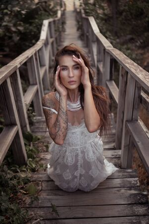 Romantic portrait of beautiful brunette woman in white lace dress on the wooden staircase in the forest Banque d'images - 143478354