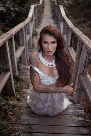 Romantic portrait of beautiful brunette woman in white lace dress on the wooden staircase in the forest Banque d'images - 143478476