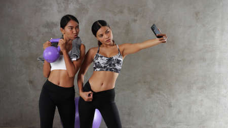 Two beautiful young Asian women doing selfie photo with smart phone at the gym. Happy female friends spending their free time at the sport centre Фото со стока