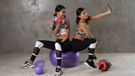 Two beautiful young Asian women posing with fitness ball and dumbbell while doing selfie photo at the gym. Happy female friends spending their free time at the sport centre Stock Photo