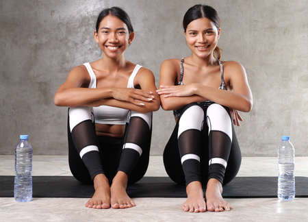 Two beautiful young Asian women taking break, drinking water on the yoga mat at the gym. Happy female friends spending their free time at the sport centre Stock Photo