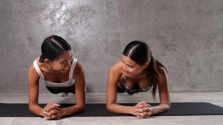 Two beautiful young Asian women exercising on the yoga mat at the gym. Happy female friends spending their free time at the sport centre