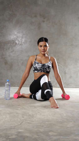 Beautiful young Asian woman exercising with dumbells at the gym. Happy girl spending her free time at the sport centre