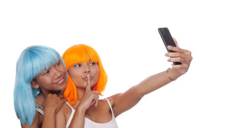Portrait of two beautiful happy Asian women friends in bright blue and orange wig doing selfie photo with smartphone over white background