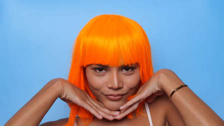 Portrait of beautiful happy Asian woman in bright orange wig posing over blue background