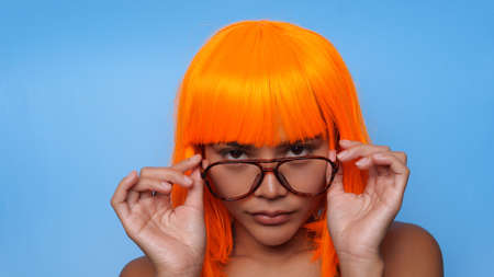 Portrait of beautiful happy Asian woman in bright orange wig and glasses posing over blue background