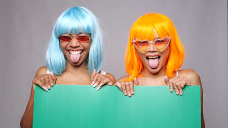 Portrait of two beautiful happy Asian women friends in bright color wigs and sunglasses posing with green board over gray background