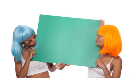 Portrait of two beautiful happy Asian women friends in bright color wigs and sunglasses posing with green board over white background Stock Photo