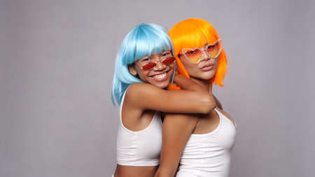 Portrait of two beautiful happy Asian women friends in bright blue and orange wigs and sunglasses posing over gray background