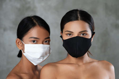 Closeup faces ot two beautiful Asian women posing in medical face mask posing over concrete background. Coronavirus and covid-19 concept