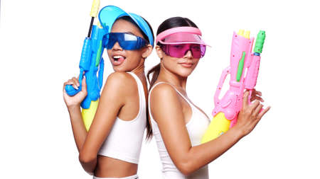 Portrait of two beautiful Asian women in pink and blue sun visor cap and sunglasses posing with water guns over white background