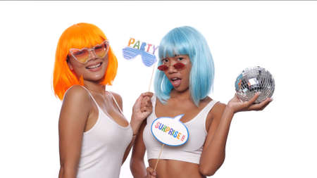 Two young smiling Asian women in bright color wigs and sunglasses posing with photo booth props and small disco ball over white background. Stock Photo