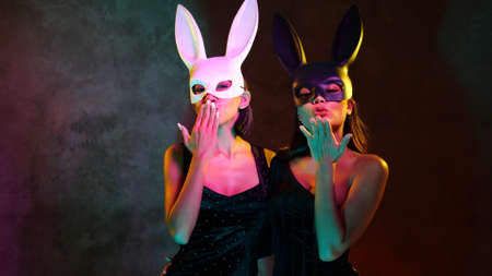 Portrait of two young flirting cute Asian women in black and white rabbit mask playfully posing for camera on the pink and yellow neon lights Stock Photo