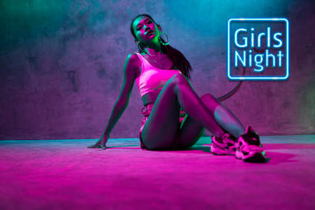 Beautiful Asian girl in tank top and shorts posing sensually on the floor over concrete wall background in the studio with pink neon lights. Girls night party banner concept