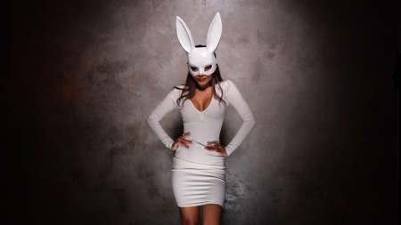 Portrait of beautiful flirting Asian woman in white dress and rabbit mask playfully posing for camera in the spotlight Stock Photo